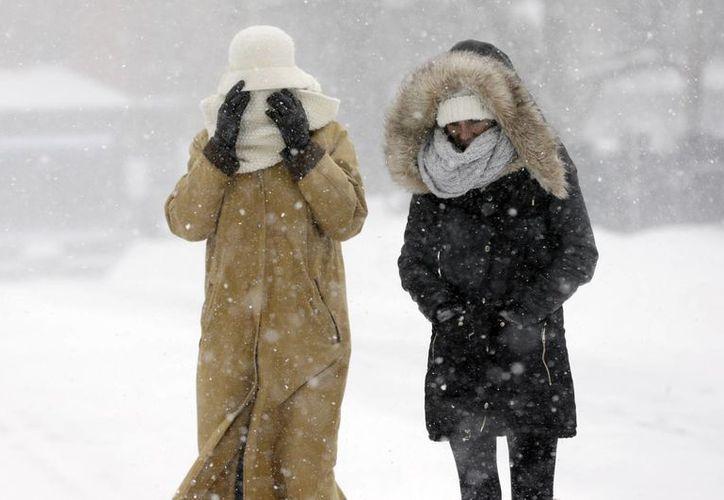 Dos personas caminan contra el viento que genera la tormenta de nieve en Boston. (Agencias)