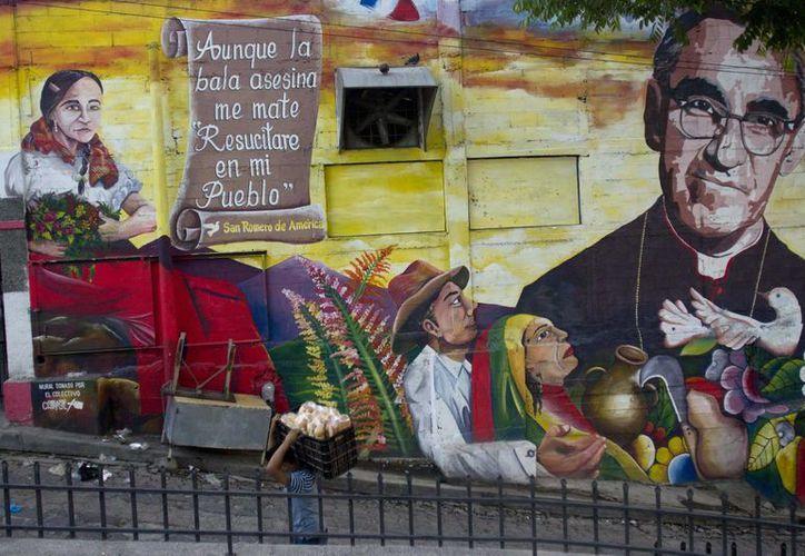 Un hombre pasa junto a un mural del arzobispo Óscar Arnulfo Romero, el cual esta en una pared en una calle de Panchimalco, El Salvador. (Agencias)