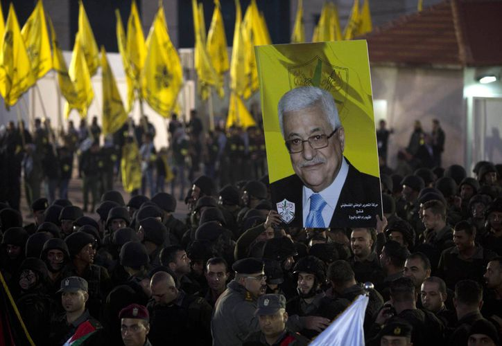 Palestinos con un cartel del presidente Mahmud Abbas, al celebrar el 50 aniversario del movimiento Fatah en la ciudad de Ramalá en Cisjordania el miércoles 31 de diciembre de 2014. (Foto: AP)