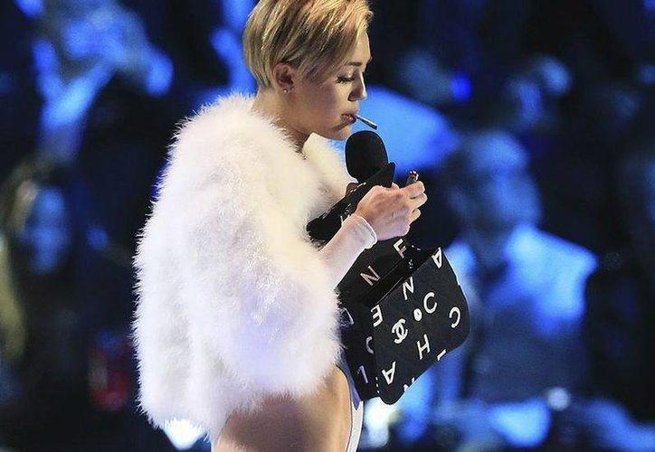 Imagen de Miley Cyrus encendiendo un cigarro en el escenario, durante la ceremonia de entrega de los Premios MTV EMA 2013 en el Ziggo Dome de Ámsterdam, Holanda. (EFE)