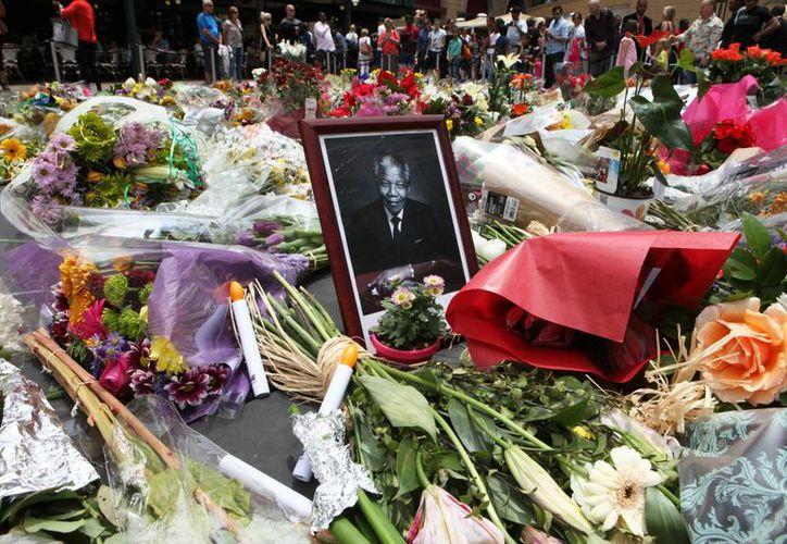 Pila de flores y retrato de Mandela en Sandton, Johannesburgo, Sudáfrica. Los homenajes hacia el expresidente fallecido son interminables dentro y fuera del país. (Agencias)