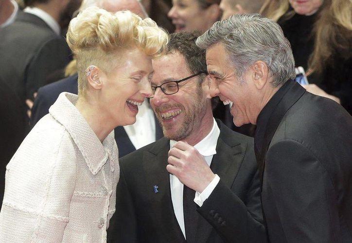 El director de cine Ethan Coen (c) bromea con el actor estadounidense George Clooney (d) y con la actriz Tilda Swinton (i), quienes actúan en su nuevo filme, Hail Caesar, que inauguró el Festival de Cine de Berlín. (EFE)