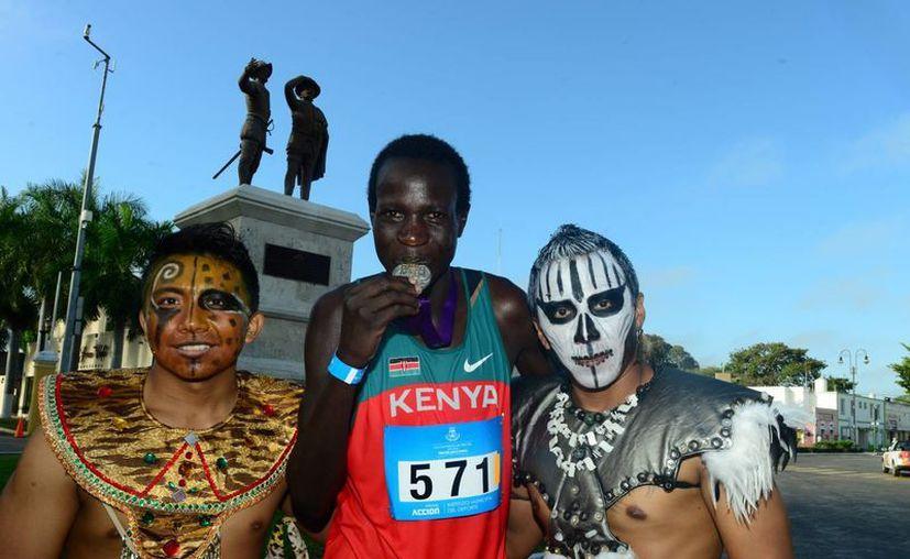 El keniano Hillary Chipchir Kimaiyo (c) posa con la medalla de primer lugar en el Maratón de Mérida. (Miraquemiro)