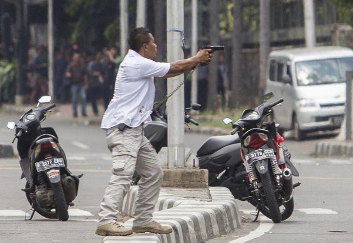 Una oficial de policía ropa apunta con su arma a los atacantes durante un tiroteo tras explosiones en Yakarta, Indonesia Jueves, 14 de enero de 2016. Los atacantes realizaron estallidos en un café Starbucks en la una zona comercial en la capital de país asiáticos. (Foto AP)