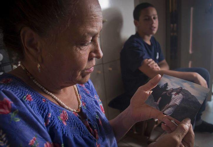Carmen Pérez muestra una foto de ella y su hijo fallecido Rolando,  quien tomaba medicamentos contra la epilepsia y estaba detenido en la prisión neoyorquina de Rikers Island cuando fue colocado en una celda de confinamiento. Dos días después falleció. (AP)