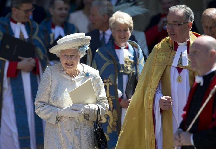 La reina Isabel II acompañada por el decano de la Abadía de Westminster, el Dr. John Hall, al salir del servicio religioso. (Agencias)