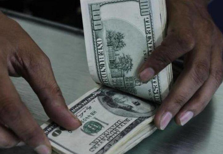 En instituciones bancarias de la capital mexicana se compró el dólar en un mínimo de 14.42 pesos. (Archivo/Agencias)