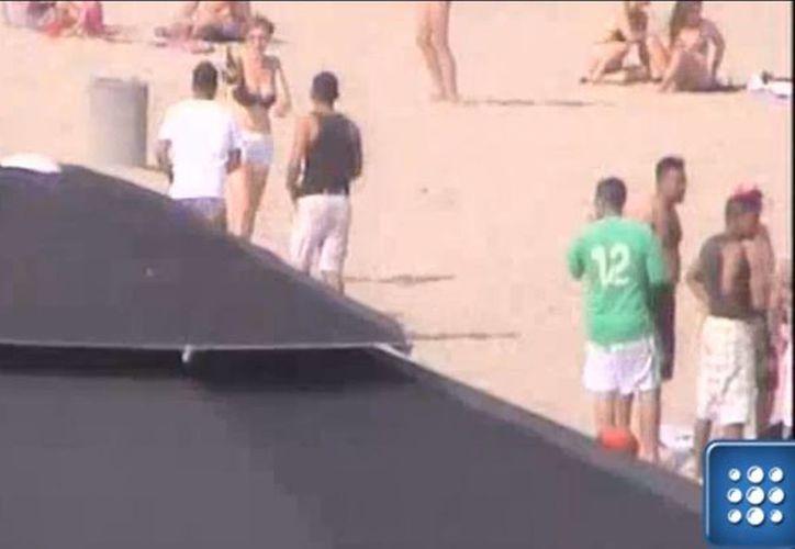 En el video se observa que una chica entrega una botella al grupo de mexicanos. (Captura de pantalla)