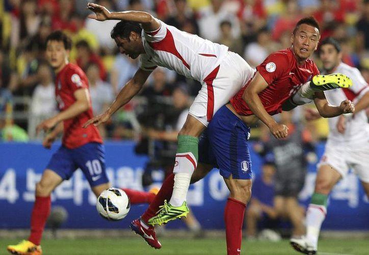 El surcoreano Kim Shin-wook (d) disputa el esférico al iraní Hashem Beikzadeh. (Agencias)