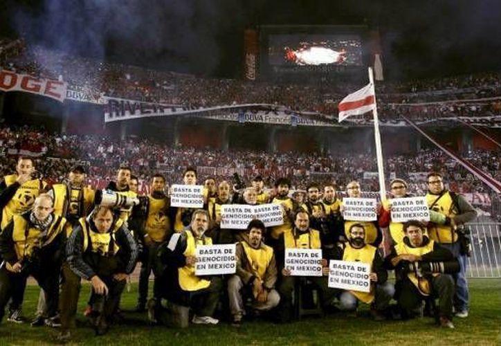 Periodistas se manifiestan en el campo de juego del estadio de River Plate, previo al partido final entre el equipo argentino y el mexicano Tigres de la UANL, en protesta por el asesinato de cinco personas en la Ciudad de México, entre ellas un fotoperiodista. (lado.mx)