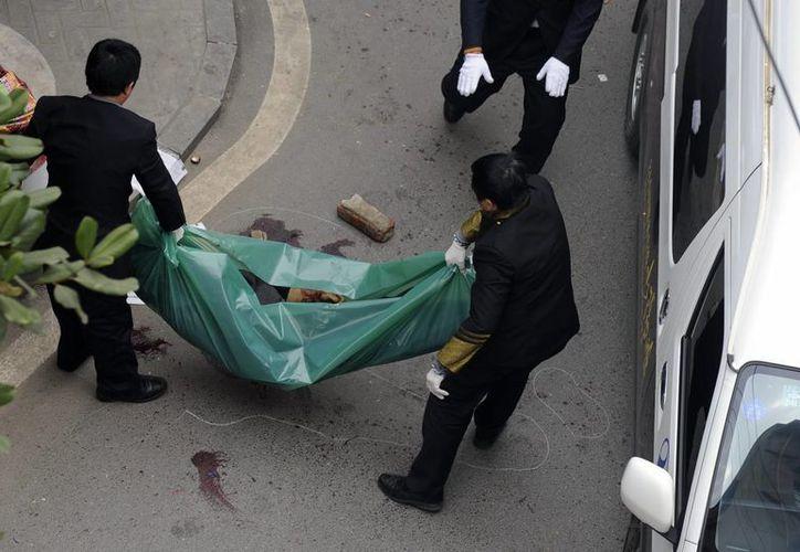 El cuerpo de una de las víctimas es levantado por las autoridades, después de la pelea que se registró en Changsha, en la provincia sureña china de Hunan. (Agencias)