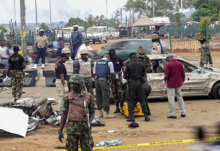 Oficiales de la policía nigeriana observan el lugar donde un coche bomba hizo explosión en Nyana, Abuya, la capital de Nigeria, el pasado 2 de mayo. (EFE/Archivo)