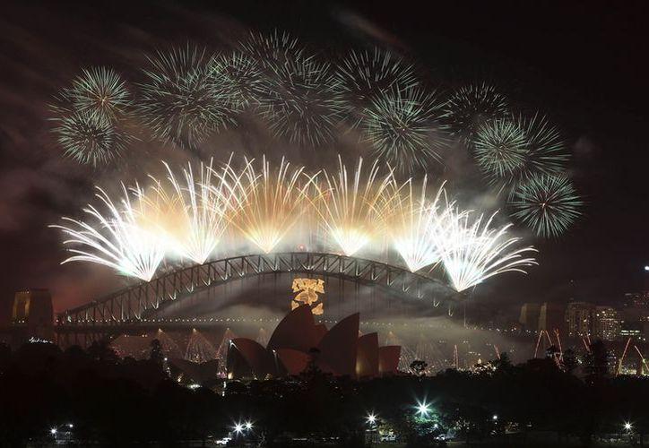 Fuegos artificiales iluminan el Puente del Puerto de Sydney, al recibir el Año Nuevo. (Agencias)