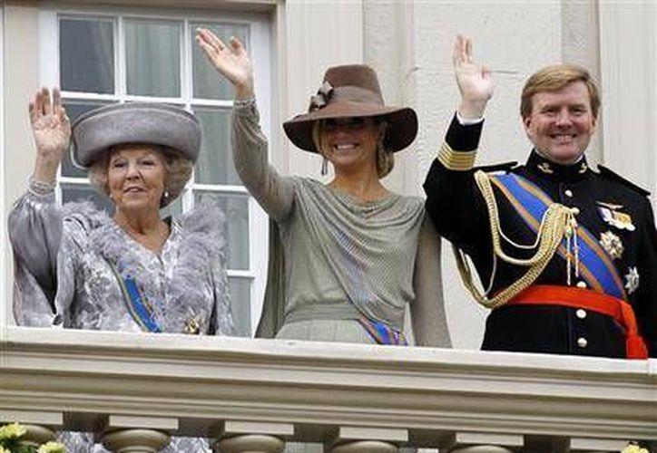 La reina holandesa Beatriz, la princesa Maxima y el príncipe Guillermo Alejandro desde el balcón del Palacio Real. (Agencias)