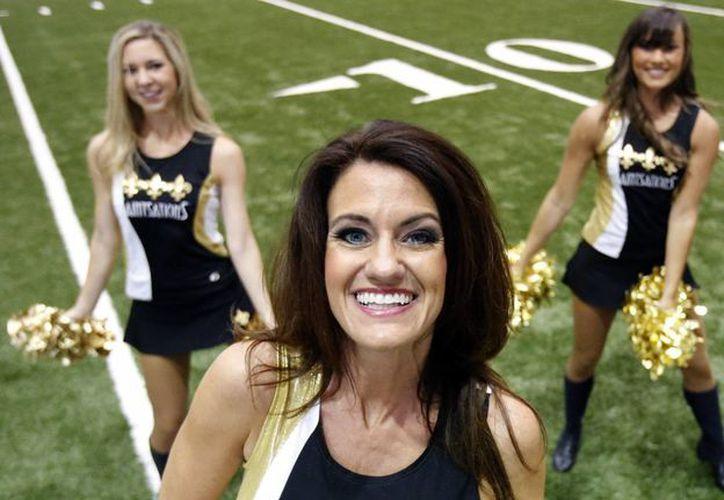 Kriste Lewis realiza una rutina con dos compañeras durante una sesión fotográfica del equipo de porristas Saintsations. (AP)
