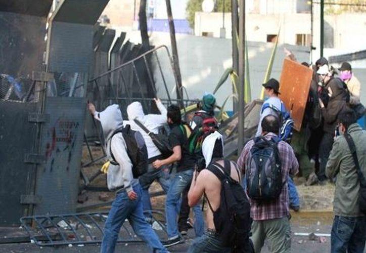 Las violentas manifestaciones del 1 de diciembre dejaron como saldo varios lesionados, entre civiles y policías. (Notimex)