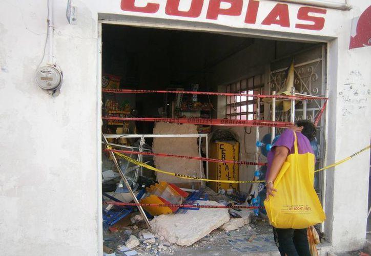 Una mujer mira el derrumbe que ocurrió en el comercio denominado 'Casa Liz', en la calle 60 entre 69 y 71 del centro de Mérida. (Daniel Martínez/SIPSE)