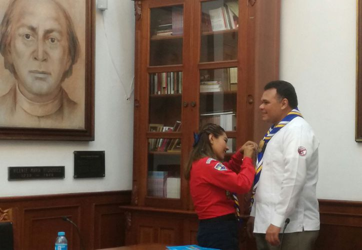 La gobernadora de Yucatán por un día, Keila Karina Jiménez Ruiz, colocó al gobernador un distintivo del Grupo Scout al que la joven pertenece. (José Acosta/SIPSE)
