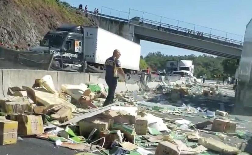Tráiler cargado de libros de texto volcó en la autopista en Veracruz y se salvó de la rapiña. (Foto: Twitter)