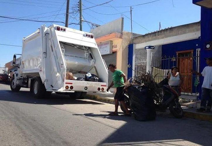Las rutas de recolección de basura va a ser las mismas, no habrán cambios ni modificaciones en alguna de las cuatro concesionarias de servicios públicos municipales para cubrir todo el municipio de Mérida. Imagen de dos personas recolectando bolsas de basura.(Milenio Novedades)