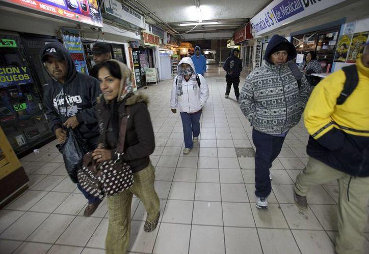 Un grupo de personas caminan hacia la frontera para cruzar a Mexicali. (Agencias)