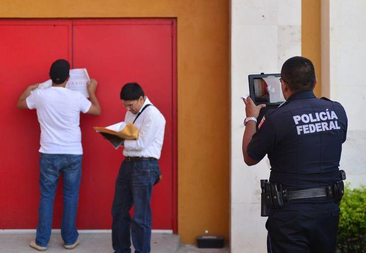 Agentes de Gobernación colocan los sellos de clausura en Casino Circus de Mérida. (Luis Pérez/SIPSE)