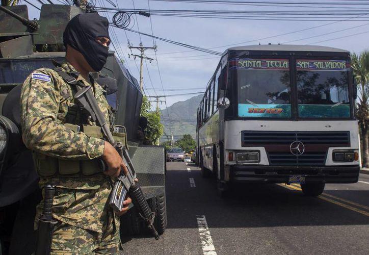 Un soldado vigila el paso de autobuses en una calle de San Salvador. Los militares fueron desplegados para garantizar la seguridad ante un paro forzado por las pandillas, que el viernes 31 de julio comenzaba a declinar (AP/Salvador Meléndez)