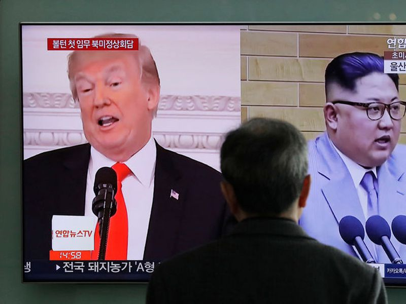 A man watches a TV screen showing file footages of U.S. President Donald Trump, left, and North Korean leader Kim Jong Un, right.