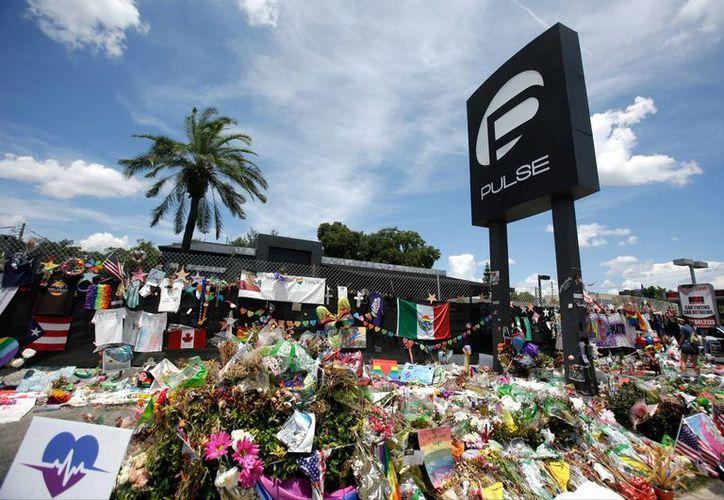 Imagen del pasado 11 de julio, de un monumento improvisado afuera de la discoteca Pulse, un día después de un ataque masivo, en Orlando, Florida. Hoy domingo por la mañana se registró un tiroteo cerca de un club nocturno en esa misma ciudad estadounidense; se reportan tres heridos. (Foto AP / John Raoux)