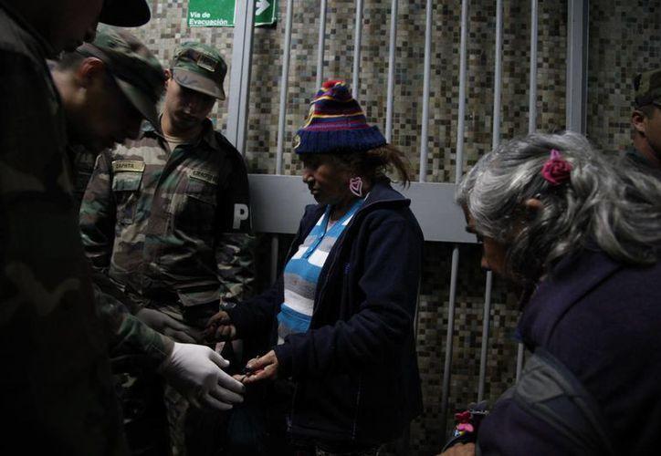 Soldados inspeccionan la bolsa de una mujer antes de dejarla pasar al refugio. (Agencias)