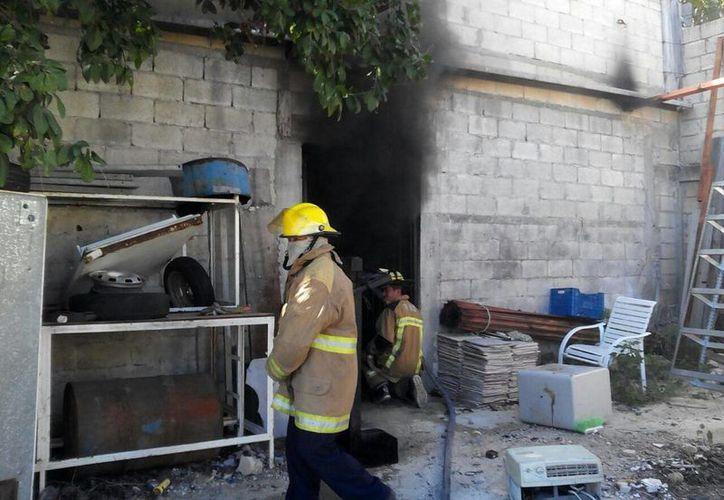 Bomberos sofocan el incendio en una bodega de materiales y aceites industriales, en el fraccionamiento Pedregales de Tanlum. (Fotos: Luis Fuente/SIPSE)