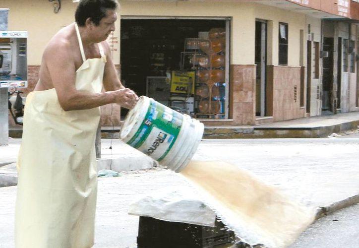 Las aguas sucias que van al subsuelo contaminan el recurso natural. En la imagen, un hombre tira una cubeta de agua sucia al drenaje. (Milenio Novedades)