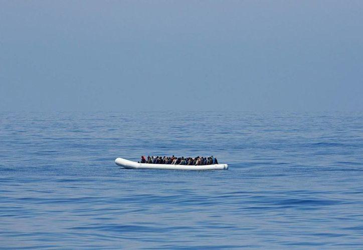 Fotografía que muestra a cerca de 200 inmigrantes en un barco inflable mientras son rescatados por el buque de la guardia italiana en el mar Mediterráneo. (EFE)