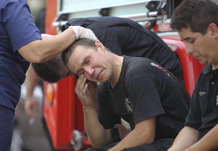 Bomberos lloran la muerte de 9 de sus compañeros, durante el combate de un incendio en un edificio de Buenos Aires, Argentina. (Efe)