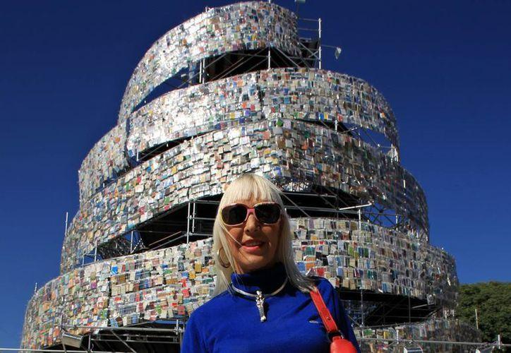 "Marta Minujín junto a la ""Torre de Babel"" que en 2011 instaló en una plaza de Buenos Aires, Argentina. (EFE/Archivo)"
