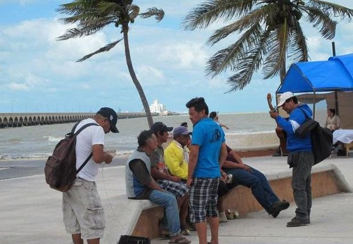 Imagen de lugareños en el malecón de Progreso, a pesar del fuerte viento que azotó la zona. (Milenio Novedades)