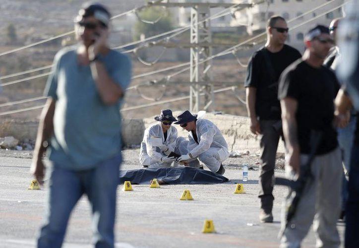 Varios policías israelíes recopilan pruebas junto al cuerpo sin vida de un palestino que ha sido abatido a tiros por un soldado israelí tras apuñalar a una joven al norte de Jerusalén. (EFE)