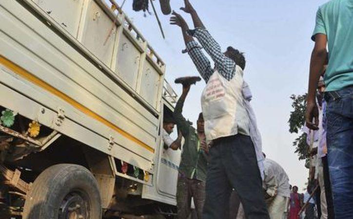 Un hombre coloca en un camión los zapatos de víctimas de una estampida en un puente en las afueras de la ciudad de Varanasi. (AP)