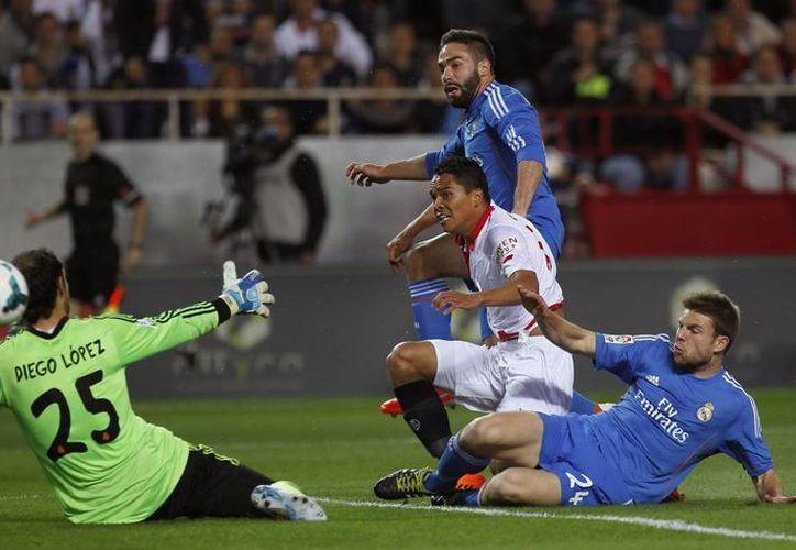 El delantero colombiano del Sevilla, Carlos Bacca (3d), supera la salida del portero Diego López (i), del Real Madrid, para conseguir el primer gol sevillista. (EFE)