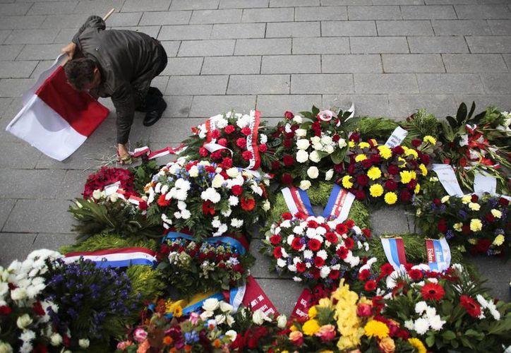 Un hombre con la bandera de Polonia coloca flores en el monumento a los soldados polacos en Berlín, Alemania, después de una ceremonia para conmemorar la invasión nazi-alemana de Polonia y el comienzo de la Segunda Guerra Mundial. (Agencias)