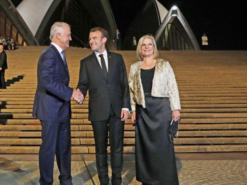 President Emmanuel Macron, center, poses with Australia's Prime Minister Malcolm Turnbull, left, and his wife, Lucy, at the Sydney Opera House in Sydney, Australia.