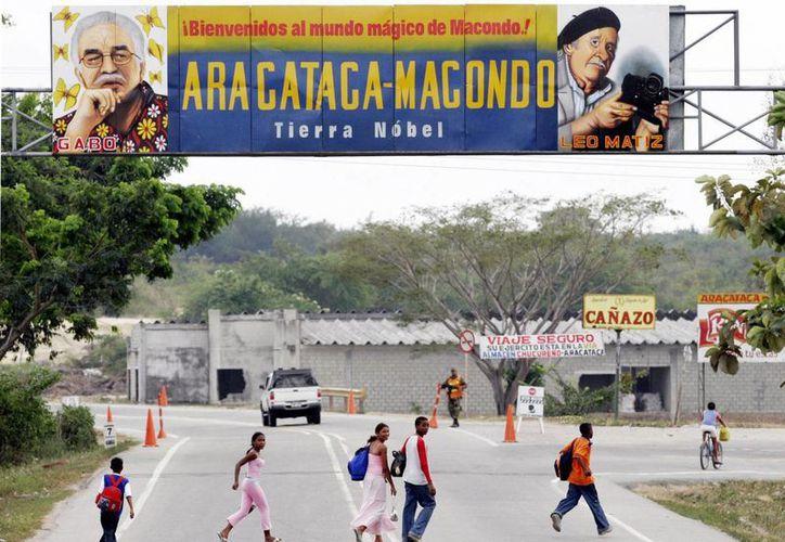 """Personas pasan por debajo de una valla publicitaria que dice """"Bienvenido al mundo mágico de Macondo"""", decorada con imágenes del premio Nobel colombiano Gabriel García Márquez, en la entrada de la ciudad natal de Márquez, Aracataca, Colombia. (Agencias)"""