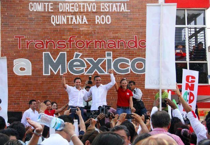 Raymundo King de la Rosa, dirigente estatal (centro) levanta la mano a José Luis Toledo y Arlet Mólgora. (Redacción/SIPSE)
