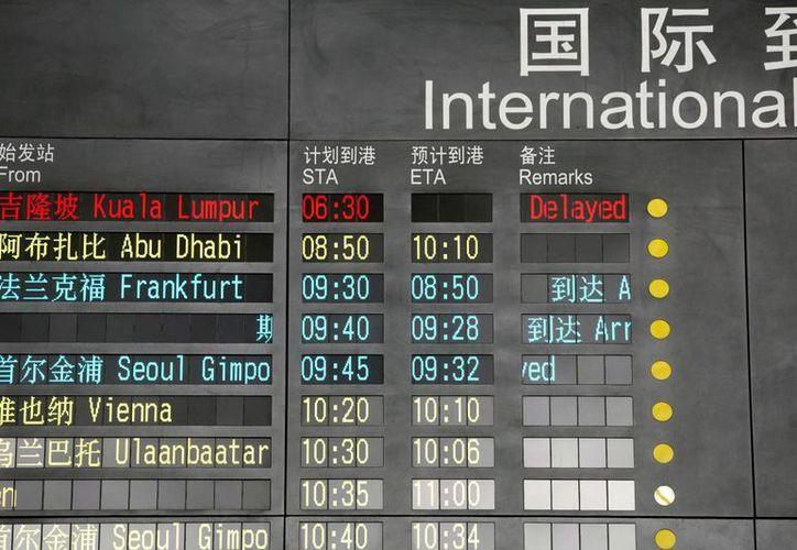 Un total de 153 chinos viajaban en el avión de Malaysia Airlines. En la imagen, el tablero de llegadas del aeropuerto de Beijing muestra como retrasado el vuelo MH370. (Agencias)
