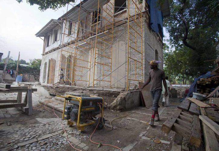 """Imagen de una """"casa de jengibre"""" dañada por el terremoto del 2010 al ser reconstruida en Puerto Príncipe, Haití. (Agencias)"""