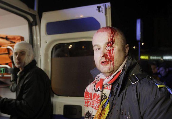 Manifestantes heridos durante una protesta en Kiev piden ayuda médica en el marco de las protestas contra el presidente de Ucrania. (Agencias)