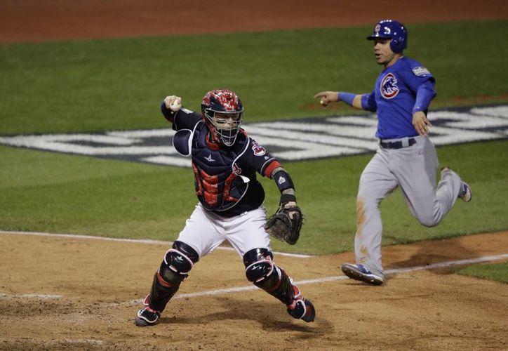 Willson Contreras (d), de Chicago, es forzado a dirigirse a home mientras lanza el catcher de Cleveland, Roberto Perez. (AP)