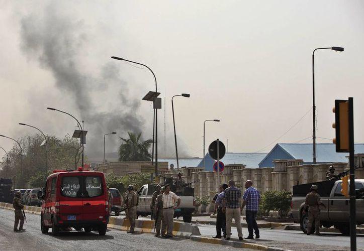 Las personas ven a lo lejos el humo negro generado por un ataque con coche bomba en Bagdad. (Agencias)