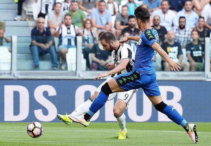 Gonzalo Higuaín (semioculto) es la gran contratación de la Juventus para esta temporada. El delantero argentino marcó un récord de goles con Nápoles la campaña pasada. (AP)