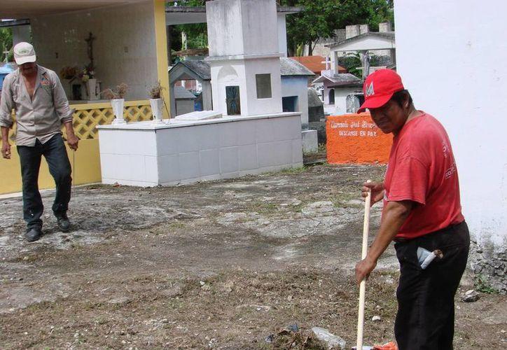 Las brigadas preparan y limpian la zona en la que se realizará la misa en honor a los fieles difuntos al iniciar el mes de noviembre. (Manuel Salazar/SIPSE)